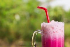 在绿色背景的泰国被冰的牛奶桃红色署名地方饮料 免版税库存照片