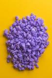 在黄色背景的淡紫色石头 库存图片