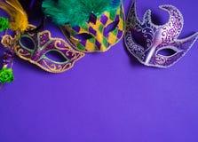 在紫色背景的狂欢节或狂欢节面具 库存照片