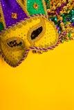 在黄色背景的狂欢节面具 库存照片