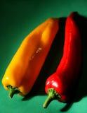 在绿色背景的甜黄色和红辣椒 免版税库存照片
