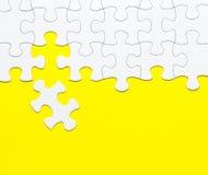 在黄色背景的白色七巧板 库存照片