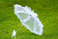 在绿色背景的白色伞 免版税库存图片