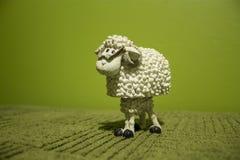 在绿色背景的白色玩具绵羊 库存照片
