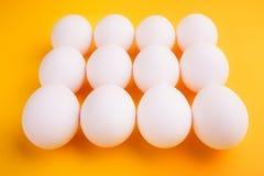 在黄色背景的白鸡蛋 免版税库存照片