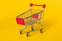 在黄色背景的空的购物台车 产品的商店篮子 免版税库存照片