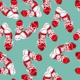 在绿色背景的红色运动鞋 库存图片