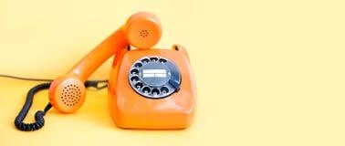 在黄色背景的葡萄酒电话繁忙的手机接收器 减速火箭的样式橙色电话通信电话中心概念 免版税库存照片