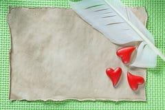 在绿色背景的葡萄酒纸羽毛红色心脏 免版税库存图片