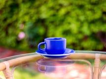 在绿色背景的蓝色杯子 库存图片