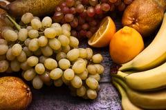在紫色背景的被分类的果子静物画 库存照片