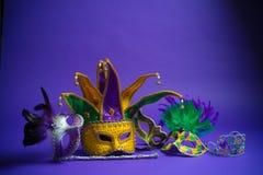 在紫色背景的被分类的狂欢节面具 图库摄影