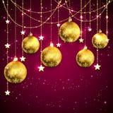 在紫色背景的金黄圣诞节球 免版税库存照片
