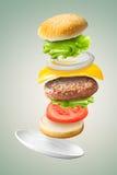 在绿色背景的飞行的经典汉堡包 免版税库存照片