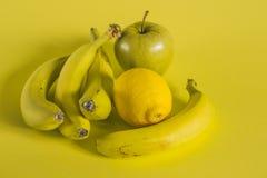在黄色背景的香蕉苹果和柠檬 免版税库存图片