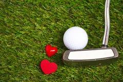在绿色背景的轻击棒和高尔夫球 免版税库存照片