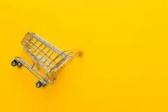 在黄色背景的购物台车 免版税库存图片