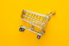 在黄色背景的购物台车 免版税图库摄影