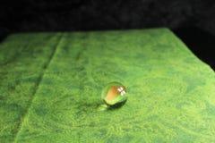 在绿色背景的玻璃大理石 免版税图库摄影