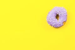 在黄色背景的紫色圆的多福饼 平的位置,顶视图 库存图片