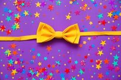 在紫色背景的黄色蝶形领结 库存照片
