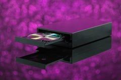 在紫色背景的黑CD DVD燃烧器 库存图片