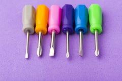 在紫色背景设置的微型色的螺丝刀 库存照片