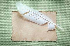 在绿色背景顶视图的葡萄酒纸板料羽毛 免版税图库摄影