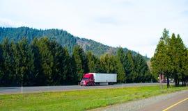 在绿色自然路的半红色卡车拖车好的船具货物 免版税库存图片