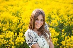 在黄色花中的美丽的妇女在领域 库存图片