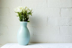 在绿色花瓶的白玫瑰在反对白色砖的白色桌布 免版税库存图片