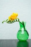 在绿色花瓶的黄色小苍兰 免版税库存照片