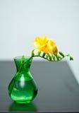 在绿色花瓶的黄色小苍兰 免版税库存图片