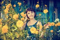 在黄色花附近的美丽的妇女 库存照片