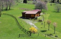 在绿色草坪中间的木瑞士山中的牧人小屋有篱芭的 免版税库存照片