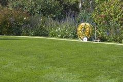 在绿色草坪的水管 免版税库存图片