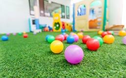 在绿色草皮的五颜六色的塑料球在学校操场 免版税库存照片