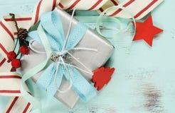 在水色蓝色木背景的现代红色和白色圣诞节装饰,与银色礼物特写镜头 免版税库存图片