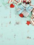 在水色蓝色木背景的现代红色和白色圣诞节装饰,与银色礼物-垂直 库存图片