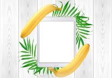 在绿色蕨叶子的片剂个人计算机和在白色木头的香蕉框架 免版税图库摄影