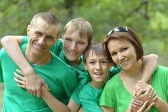 在绿色衬衣的快乐的家庭 免版税库存照片