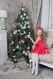 在绿色装饰的圣诞树附近的一个女孩 免版税图库摄影