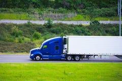 在绿色路的现代深蓝半卡车收帆水手拖车外形 免版税库存照片