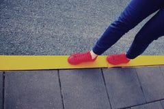 在黄色路线的红色运动鞋 免版税库存照片