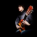 在黑色隔绝的吉他演奏员 免版税库存照片