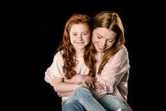 在黑色隔绝的愉快红头发人母亲和女儿拥抱 图库摄影