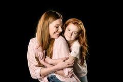 在黑色隔绝的愉快红头发人母亲和女儿拥抱 免版税库存照片