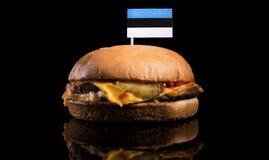 在黑色隔绝的汉堡包顶部的爱沙尼亚语旗子 库存图片