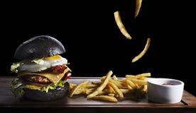 黑在黑色隔绝的汉堡和炸薯条 库存图片