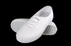 在黑色隔绝的白色帆布运动鞋 免版税图库摄影